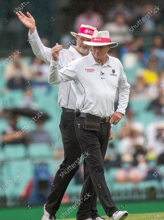 Stock Picture of Umpire Paul Wilson (L) and Paul Reiffel (R) signal ground staff to bring out the covers as rain delays play during day two of the Third Test match in the series between Australia and India at Sydney Cricket Ground