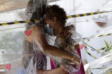 Stock Photo of Maria Amelia, right, hugs her niece Flaviana Silva through a plastic barrier during a visit to the Casa Clara home for the elderly in Brasilia, Brazil, . The home set up the system which follows COVID-19 restrictions and protection measures for the elderly residents of the home