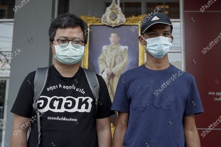 Stock Image of Pro-democracy protest leaders Anon Nampa (L) and Panupong 'Mike' Jadnok pose for a photo in front of a portrait of Thai King Maha Vajiralongkorn Bodindradebayavarangkun as they leave the Pathum Wan police station in Bangkok, Thailand, 08 January 2021. Anti-government protest leaders Anon Nampa and Panupong Jadnok presented themselves to the police to hear charges for organizing anti-government rallies during the emergency decree in 2020.