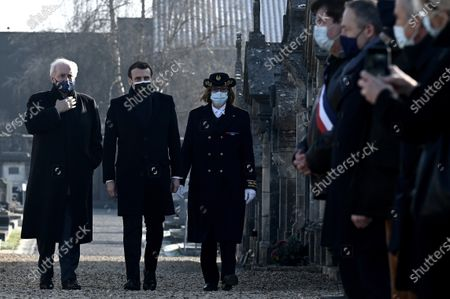 Stock Image of French President Emmanuel Macron (C) arrives with Charente's prefect Magali Debatte (R) and former minister Hubert Vedrine (L), president of the Institut Francois Mitterrand, for a tribute ceremony at the tomb of former President Francois Mitterrand marking the 25th anniversary of his death, in the cemetery of Jarnac, central western France, 08 January 2021.