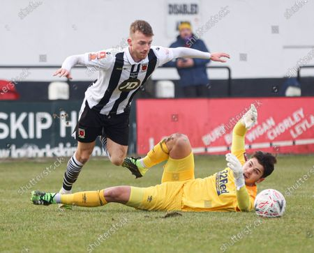 Stock Photo of Derby County goalkeeper Matt Yates fumbles the ball in a challenge with Harrison Solomon and Elliot Newby of Chorley