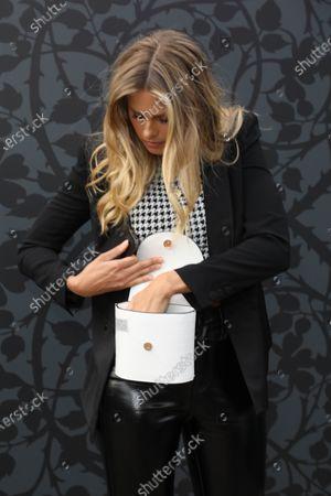 Natalie Roser looks for her face mask in her hand bag.