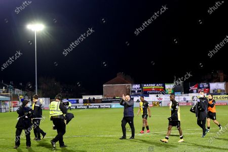 Stock Picture of Marine FC manager Neil Young and players applaud people in the stand at the end of the game