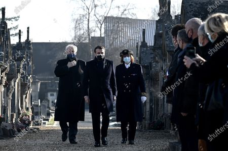 French President Emmanuel Macron, center, arrives with Charente's prefect Magali Debatte, right, and former minister Hubert Vedrine for a ceremony at the tomb of former President Francois Mitterrand to mark the 25th anniversary of his death, in the cemetery of Jarnac, western France