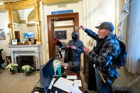 Richard Bigo Barnett (R), a supporter of US President Donald J. Trump and his baseless claims of voter fraud, takes an envelope off a desk in the office of Speaker of the House Nancy Pelosi after breaching Capitol security during a protest against Congress certifying Joe Biden as the next president in Washington, DC, USA, 06 January, 2020 (issued 08 January 2020). On 08 January Assistant House Speaker Katherine Clarke said the House will move to impeach President Trump if the Vice President and Cabinet do not remove him on their own.