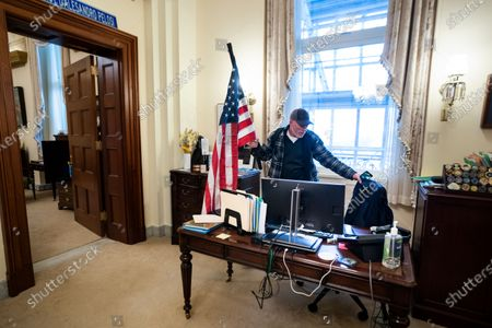 Stock Picture of Richard Bigo Barnett, a supporter of US President Donald J. Trump and his baseless claims of voter fraud, takes a seat in the office of Speaker of the House Nancy Pelosi after breaching Capitol security during a protest against Congress certifying Joe Biden as the next president in Washington, DC, USA, 06 January, 2020 (issued 08 January 2020). On 08 January Assistant House Speaker Katherine Clarke said the House will move to impeach President Trump if the Vice President and Cabinet do not remove him on their own.