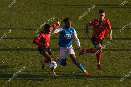 Stock Image of TJ Eyoma of Lincoln City (22) and Lewis Montsma of Lincoln City (4) run after Ricky-Jade Jones of Peterborough United (17)