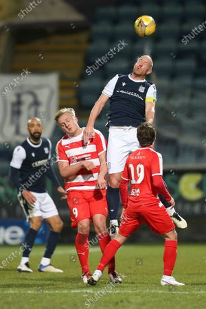 Charlie Adam of Dundee heads clear from Keiran McGachie and Scott Gray of Bonnyrigg Rose Athletic; Dens Park, Dundee, Scotland; Scottish Cup Football, Dundee FC versus Bonnyrigg Rose Athletic.
