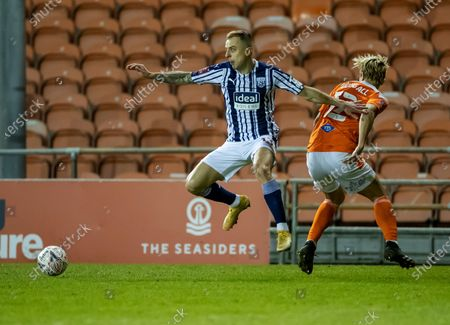 Kamil Grosicki of West Bromwich Albion leaps to avoid the tackle of Kenneth Dougall of Blackpool; Bloomfield Road, Blackpool, Lancashire, England; English FA Cup Football, Blackpool versus West Bromwich Albion.
