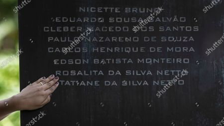 Stock Photo of Thamires da Silva Netto points out the names of her mother Rosalita da Silva Netto and sister Tatiane da Silva Netto who died of COVID-19 during a memorial in memory of COVID-19 victims at the Cemetery of Penance in Rio de Janeiro, Brazil, the day after Brazil passed 200,000 COVID-19 deaths