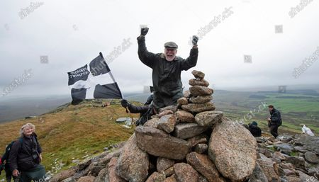 Stock Picture of Robin Hanbury-Tenison pictureda  celebrating with his family at the summit of Brown Willy 1378ft above sea level on on Bodmin Moor. 