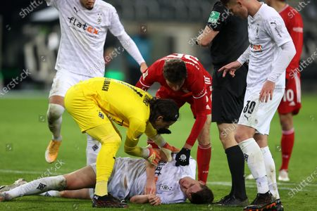 Matthias Ginter (down) of Borussia Monchengladbach is helped by team mate Yann Sommer and Thomas Mueller of Bayern Munich following a clash during the German Bundesliga soccer match between Borussia Moenchengladbach and FC Bayern Munich at Borussia-Park in Moenchengladbach, Germany, 08 January 2021.