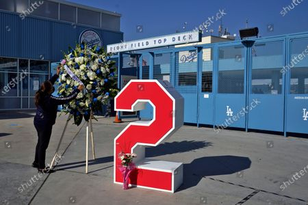 Berna Torres places a wreath in front of Tommy Lasorda's retired No. 2 at Dodger Stadium, in Los Angeles. Lasorda, the fiery Hall of Fame manager who guided the Los Angeles Dodgers to two World Series titles and later became an ambassador for the sport he loved during his 71 years with the franchise, has died. He was 93
