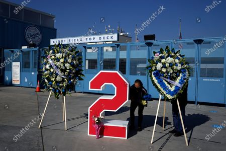Stock Picture of Berna Torres, center, places flowers on Tommy Lasorda's retired No. 2 at Dodger Stadium, in Los Angeles. Lasorda, the fiery Hall of Fame manager who guided the Los Angeles Dodgers to two World Series titles and later became an ambassador for the sport he loved during his 71 years with the franchise, has died. He was 93