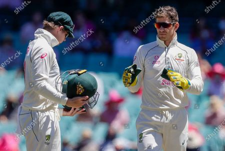 Australian captain Tim Paine, right, gestures to teammate Steve Smith, left, during play on day three of the third cricket test between India and Australia at the Sydney Cricket Ground, Sydney, Australia