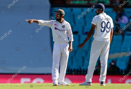 Indian captain Ajinkya Rahane, left, gestures as he talks with bowler Ravichandran Ashwin during play on day three of the third cricket test between India and Australia at the Sydney Cricket Ground, Sydney, Australia