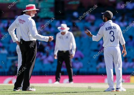 Indian captain Ajinkya Rahane, right, gestures as he speaks with umpire Paul Wilson during play on day three of the third cricket test between India and Australia at the Sydney Cricket Ground, Sydney, Australia