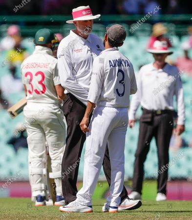 Indian captain Ajinkya Rahane talks to umpire Paul Wilson during play on day four of the third cricket test between India and Australia at the Sydney Cricket Ground, Sydney, Australia