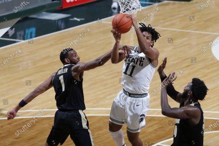 Michigan State's A.J. Hoggard, center, puts up a shot and draws a foul against Purdue's Aaron Wheeler, left, and Trevion Williams during an NCAA college basketball game, in East Lansing, Mich. Purdue won 55-54