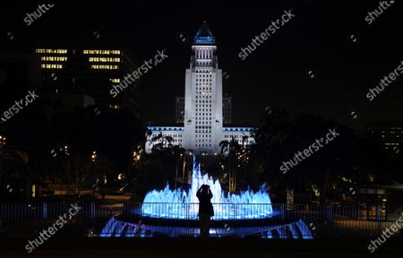 """Photographer lines up a photo of Los Angeles City Hall illuminated in """"Dodger blue"""" in tribute to the late longtime Los Angeles Dodgers baseball manager Tommy Lasorda, in Los Angeles. Lasorda, the fiery Hall of Fame manager who guided the Dodgers to two World Series titles and later became an ambassador for the sport he loved during his 71 years with the franchise, has died. He was 93"""