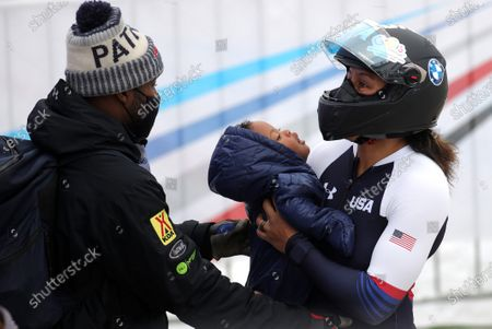 Elana Meyers Taylor of the USA with her child after the second run in the women's Bobsleigh World Cup event in Winterberg, Germany, 09 January 2021.