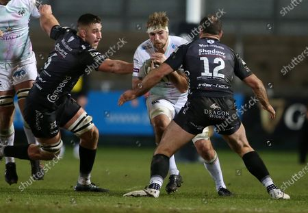 Will Griffiths of Ospreys is challenged by Jamie Roberts of Dragons.
