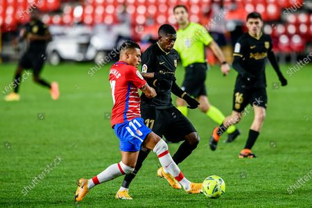 Barcelona's Ousmane Dembele. vies for the ball with Granada's Darwin Machis during the Spanish La Liga soccer match between Granada and FC Barcelona at the Los Carmenes stadium in Granada, Spain