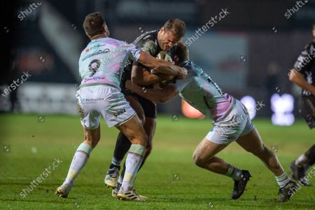 Jamie Roberts of Dragons is tackled by Rhys Webb of Ospreys and Kieran Williams of Ospreys