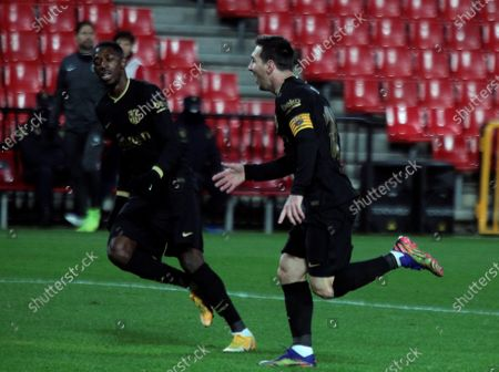 FC Barcelona's striker Lionel Messi (R) celebrates with teammate Ousmane Dembele after scoring the 0-3 goal during the Spanish LaLiga soccer match between Granada CF and FC Barcelona held at Nuevo los Carmenes stadium, in Granada, southern Spain, 09 January 2021.