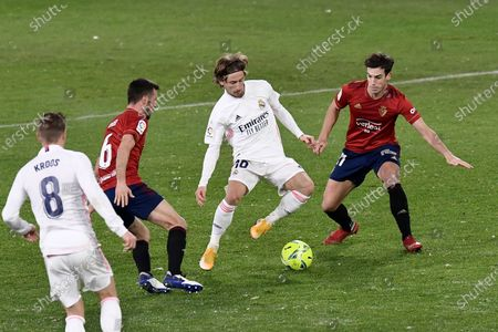 Stock Image of Real Madrid's Luka Modric, centre, controls the ball during a Spanish La Liga soccer match between Osasuna and Real Madrid at El Sadar stadium in Pamplona, Spain