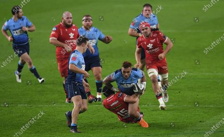 Willis Halaholo of Cardiff Blues is tackled by Leigh Halfpenny of Scarlets.