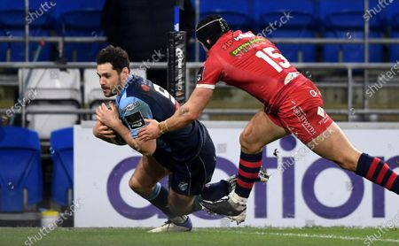 Stock Photo of Tomos Williams of Cardiff Blues beats Leigh Halfpenny of Scarlets to score try.