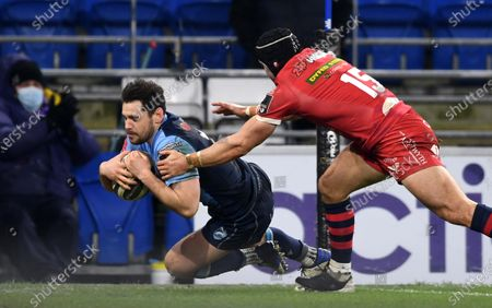 Tomos Williams of Cardiff Blues beats Leigh Halfpenny of Scarlets to score try.