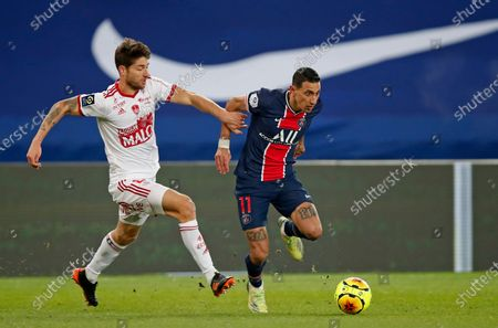 PSG's Angel Di Maria, right, is challenged by Brest's Paul Lasne as he runs with the ball during the French League One soccer match between Paris Saint-Germain and Brest at the Parc des Princes in Paris