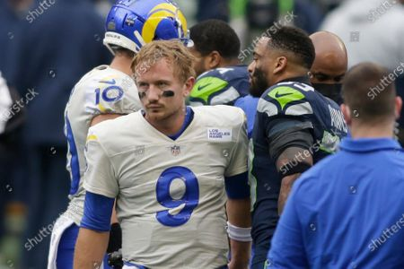 Seattle Seahawks strong safety Jamal Adams (33) talks with Los Angeles Rams quarterback John Wolford after Wolford was injured and leaving the game during the first half of an NFL wild-card playoff football game, in Seattle