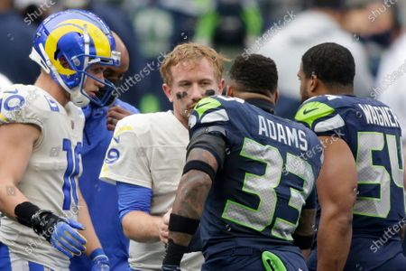 Seattle Seahawks strong safety Jamal Adams (33) talks with Los Angeles Rams quarterback John Wolford after Wolford was injured and was leaving during the first half of an NFL wild-card playoff football game, in Seattle