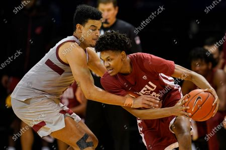 Washington State forward Carlos Rosario, right, is defended by Stanford forward Spencer Jones during the second half of an NCAA college basketball game in Santa Cruz, Calif