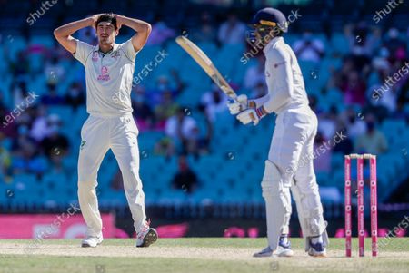 Australia's Mitchell Starc, left, reacts after bowling to India's Shubman Gill during play on day four of the third cricket test between India and Australia at the Sydney Cricket Ground, Sydney, Australia