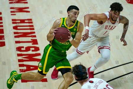 Oregon guard Chris Duarte drives to the basket as Utah forward Timmy Allen (1) defends during the first half of an NCAA college basketball game, in Salt Lake City