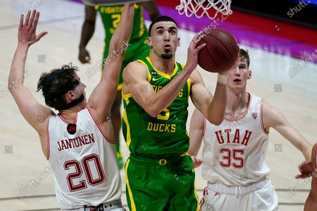 Stock Image of Oregon guard Chris Duarte, center, goes to the basket as Utah's Mikael Jantunen (20) and Branden Carlson (35) defend in the first half during an NCAA college basketball game, in Salt Lake City