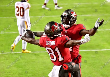 Tampa Bay Buccaneers wide receiver Antonio Brown (81) celebrates with teammate Chris Godwin (R) after a 36-yard touchdown against the Washington Football Team during the first half of a wild card playoff game at FedEx Field in Landover, Maryland on Saturday, January 9, 2021.