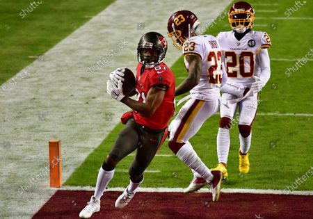 Tampa Bay Buccaneers wide receiver Antonio Brown (81) scores a 36-yard touchdown in front of Washington Football Team cornerbacks Ronald Darby (23) and Jimmy Moreland (20) during the first half of a wild card playoff game at FedEx Field in Landover, Maryland on Saturday, January 9, 2021.