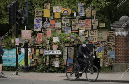 A cyclist wearing a face mask to protect from coronavirus waits at traffic lights next to signs supporting the National Health Service (NHS) displayed together on railings after being made and put up there gradually for the last three weeks by artist and local resident Peter Liversidge in a work he calls 'Sign Paintings for the NHS' in east London