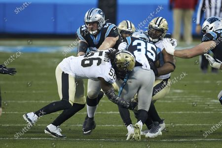 Stock Photo of Carolina Panthers running back Rodney Smith (35) is stopped by New Orleans Saints linebacker Demario Davis (56) and defensive tackle David Onyemata (93) during an NFL football game, in Charlotte, N.C