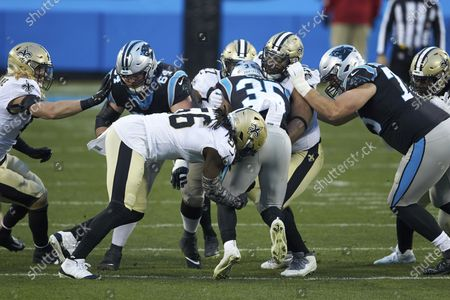 Carolina Panthers running back Rodney Smith (35) is stopped by New Orleans Saints linebacker Demario Davis (56) and defensive tackle David Onyemata (93) during an NFL football game, in Charlotte, N.C