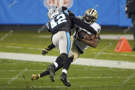 New Orleans Saints wide receiver Emmanuel Sanders (17) is hit by Carolina Panthers safety Sam Franklin (42) during an NFL football game, in Charlotte, N.C