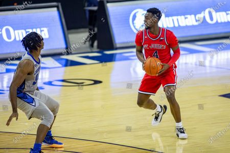 St. John's guard Greg Williams Jr. (4) brings the ball down the court against Creighton guard Denzel Mahoney (34) in the second half during an NCAA college basketball game, in Omaha, Neb