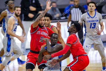 Creighton forward Damien Jefferson (23) defends the ball from St. John's guard Greg Williams Jr. (4) and St. John's guard Julian Champagnie (2) in the second half during an NCAA college basketball game, in Omaha, Neb