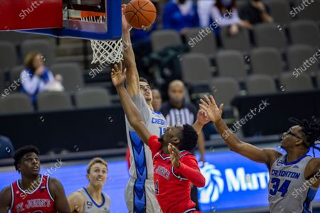 Creighton forward Christian Bishop (13) blocks a lay up by St. John's guard Greg Williams Jr. (4) in the second half during an NCAA college basketball game, in Omaha, Neb