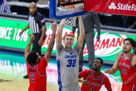 Creighton center Ryan Kalkbrenner (32) makes a dunk agaist St. John's guard Julian Champagnie (2) and St. John's guard Greg Williams Jr. (4) in the first half during an NCAA college basketball game, in Omaha, Neb